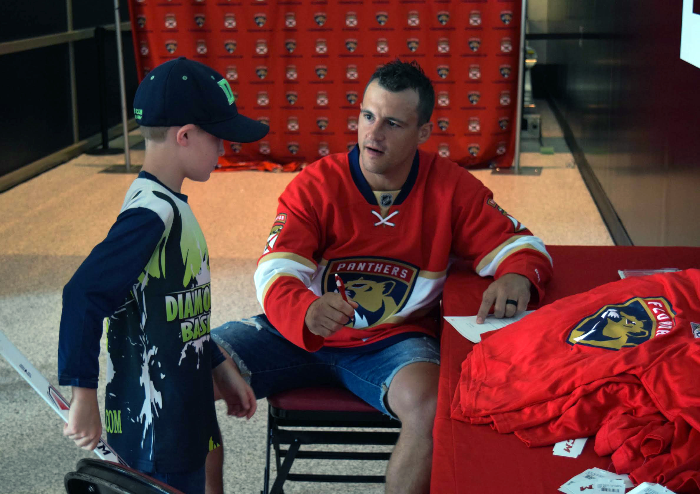 The Florida Panthers' Michael Haley helps a Learn To Play participant sign a mock contract to the hockey team. Photo provided by the Florida Panthers.
