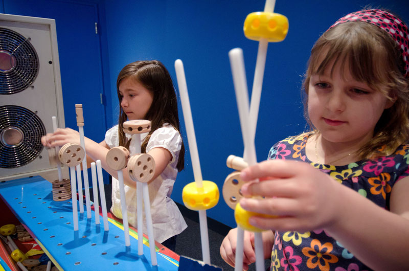 Children play with learning-based games at the Curious George exhibit. Photo courtesy of Museum of Discovery and Science.